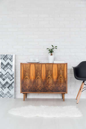 commode: Rustic, wood commode standing in ligth room with white, brick wall