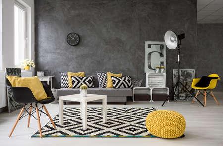 Ruime, grijze woonkamer met een bank, stoelen, staande lamp, kleine salontafel, decoraties in geel, zwart en wit