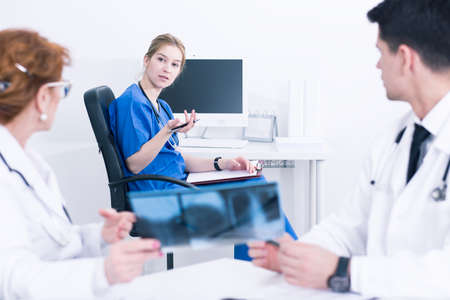 group strategy: Doctors in medical uniforms back view and nurse in blue uniform sitting in light interior Stock Photo