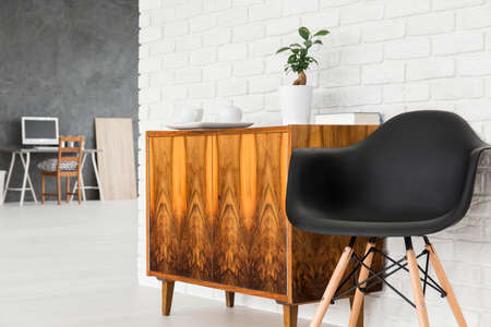 office wall: Light interior with old, wood commode, black chair and brick wall texture, home office in the background Stock Photo