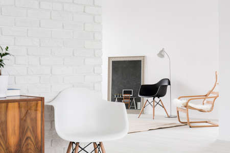 wood furniture: White interior with comfortable chairs, wood furniture and decorative brick wall Stock Photo