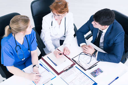 beside table: Women in medical uniforms and man in suit sitting beside table in light office