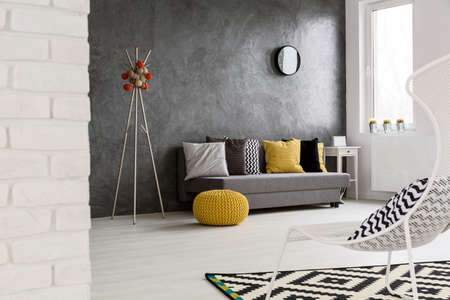 wall decor: Modern, grey interior with sofa, chair, yellow details and stylish decorations Stock Photo