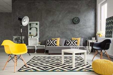 Szary pokój dzienny z rozkładanymi, krzesła, stojąca lampa, stolik, żółte detale i ozdoby wzór w czerni i bieli