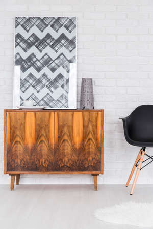 commode: Wood commode, modern picture and black chair standing in white room