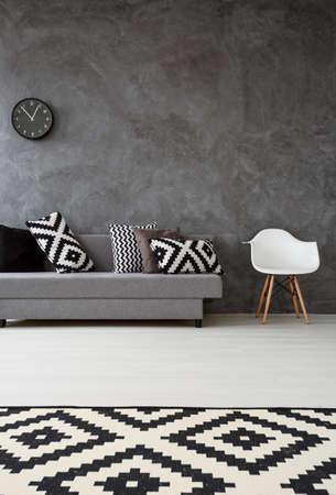 Šedý obývací pokoj s pohovkou, židle, koberec vzor a polštáře v černé a bílé barvě