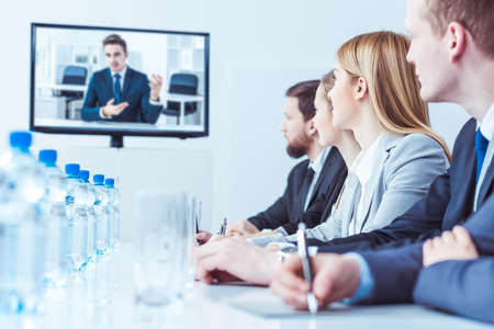 business conference: Elegant people during video chat with business partner, sitting in light interior