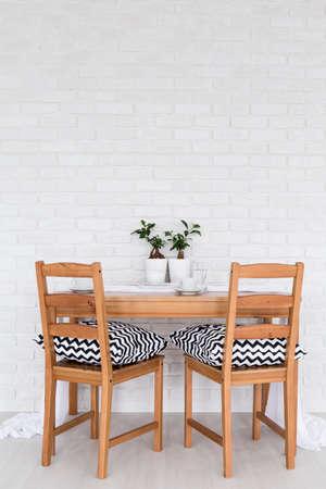 Eenvoudige houten tafel en twee stoelen staan in het licht interieur met decoratieve bakstenen muur