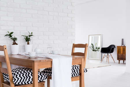 table and chairs: Spacious interior with wood table, chairs, mirror and decorative brick wall