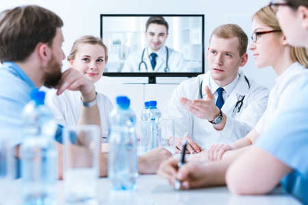 health professionals: Group of medics in white uniforms during video conference with young doctor, sitting in light interior Stock Photo