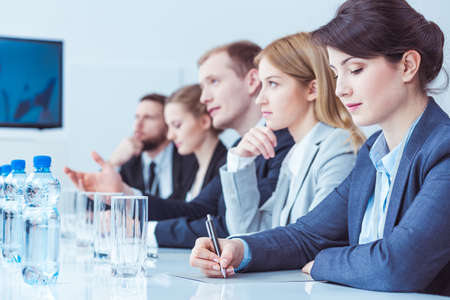 firm: Firm management during business meeting, sitting beside long desk in light office Stock Photo