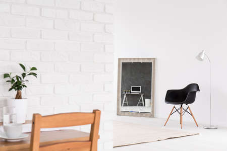 interior wall: Home interior with decorative mirror, chairs, standing lamp, wood table and white brick wall Stock Photo
