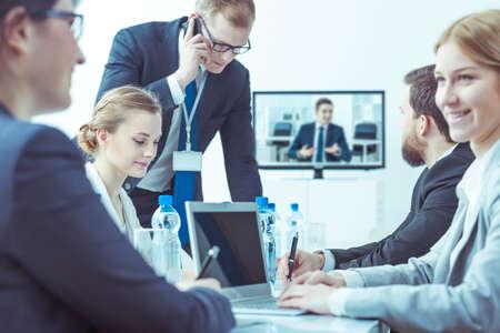 Üzletasszonyok és üzletemberek alatt videokonferencia ülve világos belső