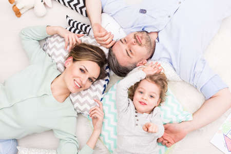 Smiling woman, man and small boy relaxing together in light bedroom Stock Photo