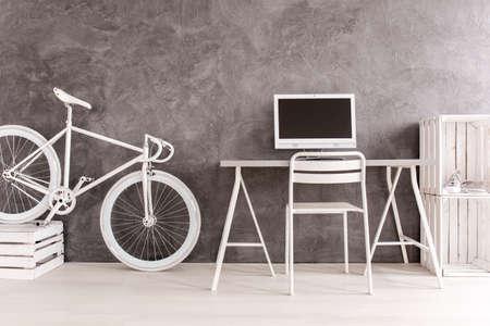 mobiliario de oficina: Interior gris con la bici blanca, escritorio, silla, ordenador y librería de bricolaje