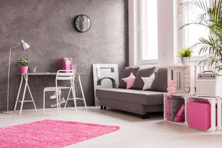desk lamp: Spacious interior in grey, pink and white with desk, office, lamp, sofa and bookcase