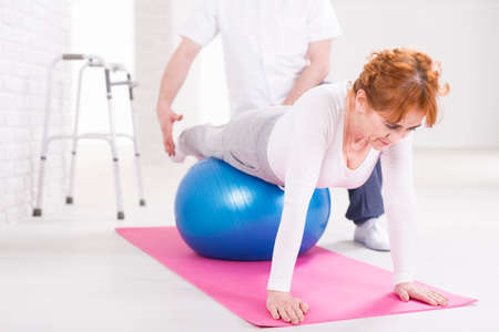 gym ball: Woman exercising with gym ball in light interior and phsyiotherapist helping her