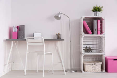 Light room with simple desk, standing lamp, white chair and DIY bookcase