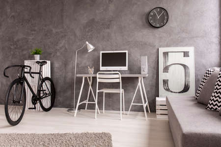 comfortable chair: Grey interior with black bike, white desk and chair, comfortable sofa and grey carpet, decorative picture with number five Stock Photo
