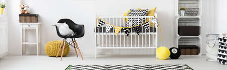 Spacious, light baby room with white cot, black chair and home decorations, panorama