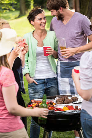 Young couple laughing at the barbecue party