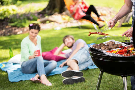 backyard woman: Barbecue in park with friends on a sunny afternoon