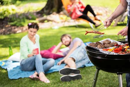 uomo felice: Barbecue nel parco con gli amici in un pomeriggio soleggiato