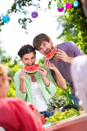 summer fruits: Happy people eating watermelon on a picnic Stock Photo
