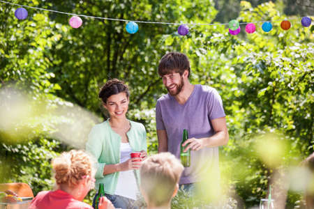 family outside: Young people enjoying summer garden barbecue party