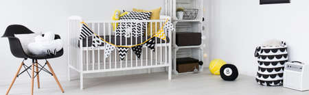 scandinavian people: Spacious, light baby room with white cot, black chair and home decorations, panorama