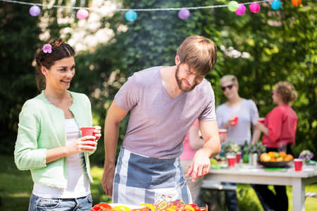 happy feast: Carefree couple enjoying themselves at barbecue party