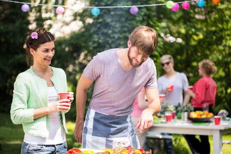 Sorglose Paare sich bei Grillparty genießen