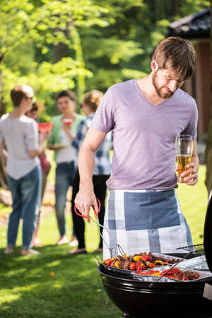 people: Man preparing food on garden barbecue with friends Stock Photo