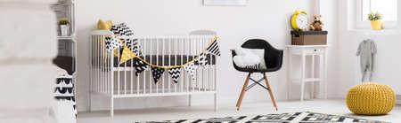 Ruime, lichte babykamer met witte kinderbed, zwarte stoel en home decoratie, panorama