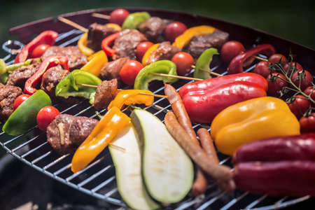 Delicious skewers and vegetables barbecued on a grill