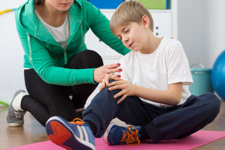 boy lady: Small boy injured during physical exercises and woman physiotherapist trying to help him.