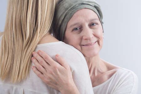 Older sick smiling woman with cancer hugging with her young daughter