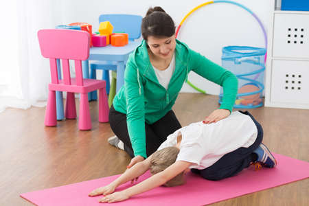 faulty: Woman assisting boy during physiotherapy exercises.