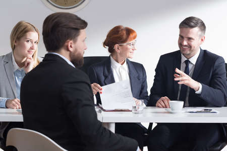 employers: Handsome businessman joking with new applicant and other employers during job interviewHandsome businessman joking with new applicant and other employers during job interview Stock Photo