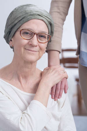 heal care: Older woman with scarf with cancer and her daughter holding hand on mothers shoulder