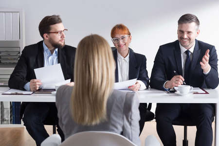 employers: Three employers interviewing young woman on job interview in corporation