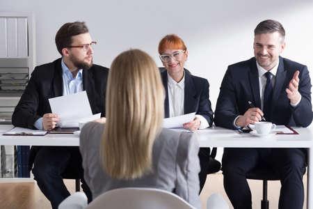Tres empresarios de entrevista mujer joven en la entrevista de trabajo en la corporación Foto de archivo