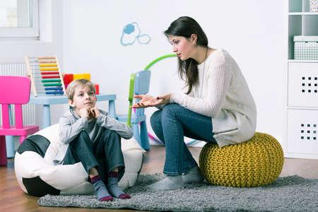 Hilfreiche professionelle junge Psychologe versucht, mit Problemen zu kleinen Jungen zu bekommen durch
