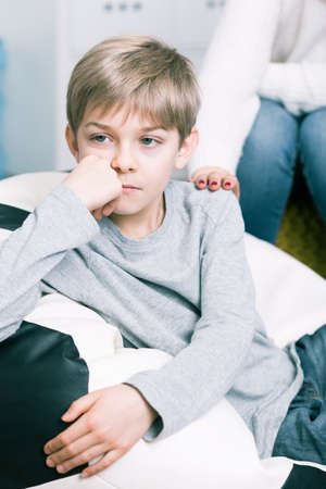 color consultation: Little worried boy having problems at school. Supportive mother holding hand on his shoulder Stock Photo