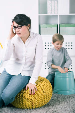 music therapy: Little boy playing on bucket as a drums. Next to him his tired teacher with headache