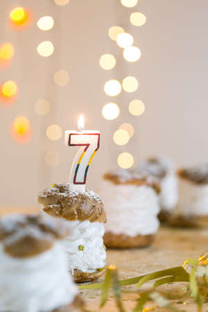 top 7: Close-up of pastry with cream prepared for birthday party. On the top candle with number 7