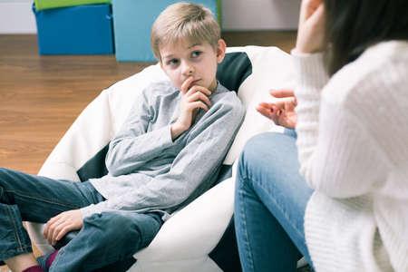 Besorgte Junge Sitzung mit mit Schulpädagogin. Sitzen auf großen bequemen Puff Lizenzfreie Bilder