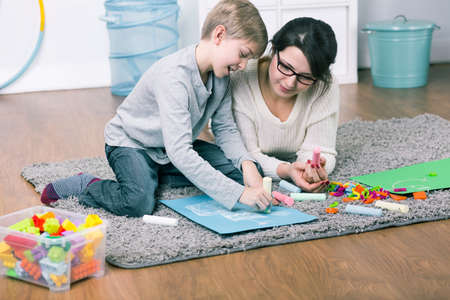 single mother: Single mother spending time with his son. Drawing together a picture Stock Photo