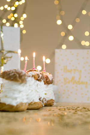 party pastries: Yummy cupcakes filled with whipped cream and lighted candles waiting for birthday person