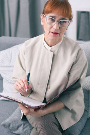 observations: Senior wise marriage psychotherapist writing down her observations about couple Stock Photo